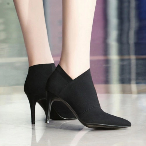 sexy leather pointed toe ankle boots that are black with a women standing in them