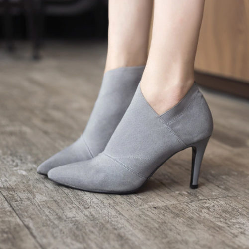 sexy leather pointed toe ankle boots that are grey with a women standing in them
